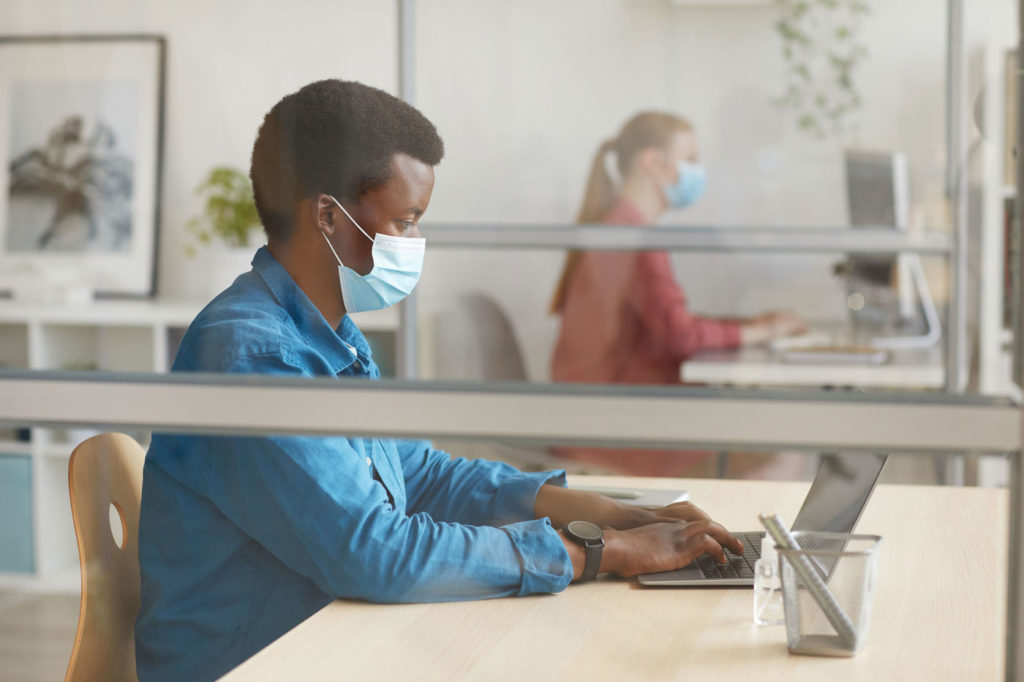 Man-at-copy-center-using-laptop-cubicle
